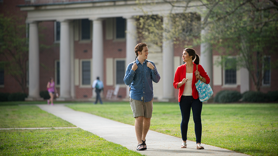 Male and female student walking across campus